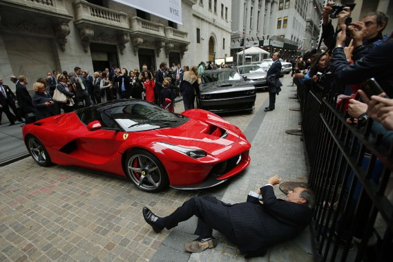 Un enthousiaste tente de prendre une photo d'une LaFerrari stationnée non loin de la Bourse de New York, lors du lancement en Bourse de Fiat-Chrysler le 13 octobre 2014. (REUTERS)