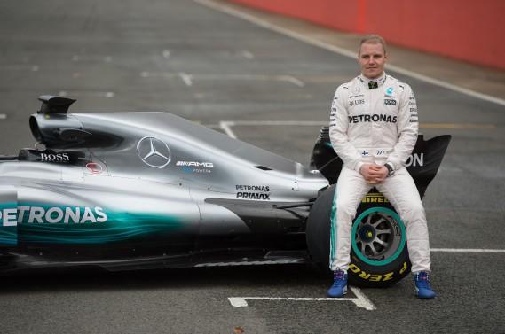 Valtteri Bottas pose assis sur un pneu de la nouvelle voiture de F1 de Mercedes. (AFP)