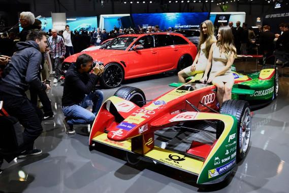 Des hôtesses posent sur une voiture de course de Formule Électrique. (AFP)