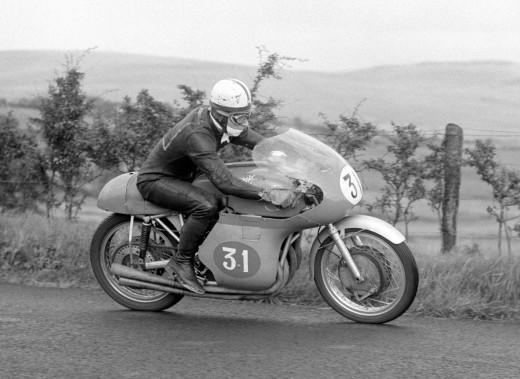 John Surtees au volant de sa moto MV Agusta durant une pratique avant le Grand Prix d'Ulster, en Irelande du Nord, le 8 août 1958. Surtees a été 7 fois champion du monde de moto pour MV Augusta. (AP)