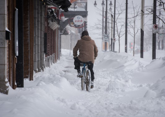 Un cycliste a tenté de circuler sur les trottoirs du centre-ville de Trois-Rivières malgré les accumulations de neige. (François Gervais, Le Nouvelliste)