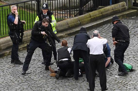 Un policier pointe son arme sur un homme au sol. (Photo Stefan Rousseau, AP)