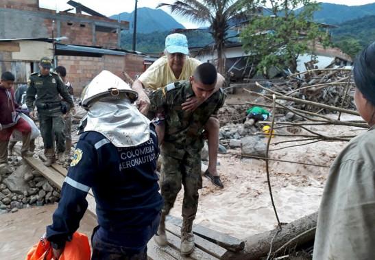Un militaire transporte une femme en passant sur un pont de fortune. (AP, Colombian Army)