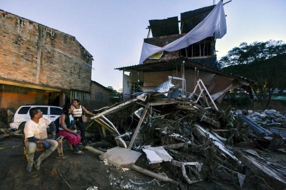 Des membres d'une famille sont assis tout près de leur maison en ruine. (AFP, LUIS ROBAYO)