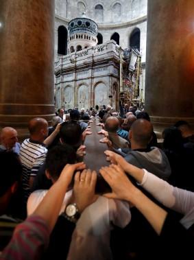 Des pèlerins transportent une croix dans l'Église du Saint Sépulcre, à Jérusalem, vendredi. (AFP, THOMAS COEX)