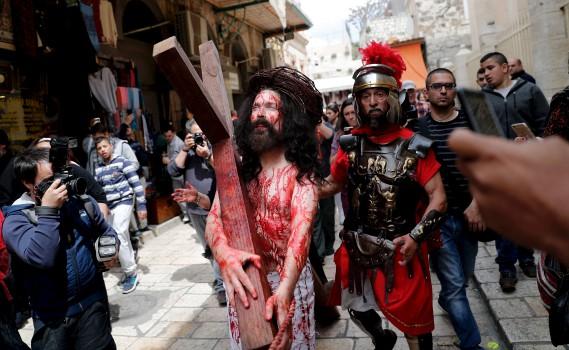 Un pèlerin chrétien simule les souffrances de Jéus dans les rues de la Vieille ville de Jérusalem, vendredi. (AFP, THOMAS COEX)