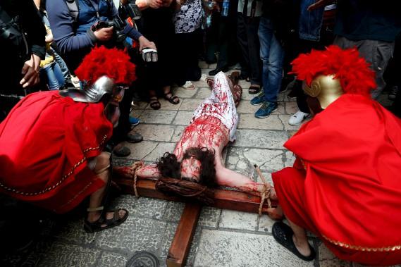 Un pèlerin chrétien simule la crucifixion dans la Vieille ville de Jérusalem, vendredi. (AFP, THOMAS COEX)