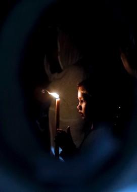Un enfant tient un cierge, alors qu'il entre dans le Tombeau de Jésus, dans l'Église du Saint Sépulcre, vendredi. (AFP, THOMAS COEX)
