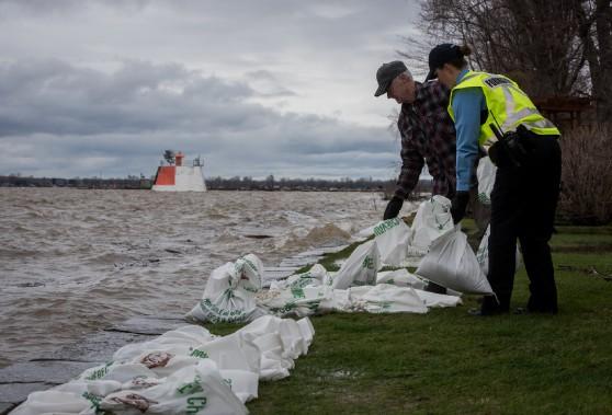 Un riverain, Alain Sirois, a reçu l'aide d'une étudiante de l'École nationale de police de Nicolet, Kim Zeestraten, pour transporter les sacs de sable sur son terrain. (François Gervais, Le Nouvelliste)