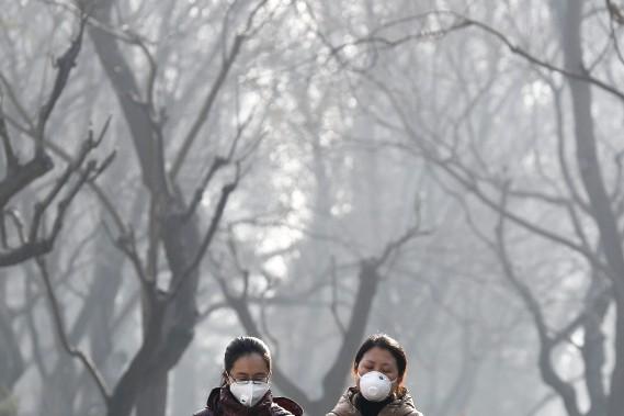 Les épisodes de smog extrême sont fréquents à Pékin, comme celui vécu l'hiver dernier. Cette photo prise le 19 décembre 2016 montre deux femmes portant des masques respiratoires. (AP)