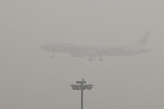 Un avion d'Air China atterrit à Pékin le 21 décembre 2016. L'alerte de smog extrême a touché 460 millions de Chinois l'hiver dernier selon Greenpeace, qui ajoute que 200 millions d'entre eux ont été exposés à des niveaux de pollution au moins 10 fois supérieurs aux normes. La pollution est causée par les centrales au charbon et par l'explosion du nombre de véhicules. (AP)