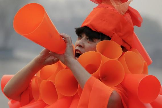 L'artise chinoise Kong Ning vêtue d'un costume fait de centaines de porte-voix orange, harangue les spectateurs sur le danger de la pollution lors d'une performance à Pékin lors d'une alerte de smog intense le 7 décembre 2015, alors que le code orange d'avertissement était en vigueur. En Chine, seul le code rouge est plus élevé que le code orange. (REUTERS)