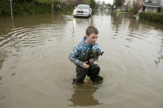 Un garçon sur le boulevard Greber devenu rivière, à Gatineau. (Le Droit, MARTIN ROY)
