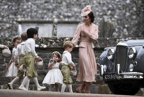 La duchesse de Cambridge, Kate Middleton, s'amuse avec les filles et les garçons d'honneur, incluant le prince George (deuxième à partir de la droite) et la princesse Charlotte (troisième à partir de la droite). (Justin Tallis/Pool Photo via AP)
