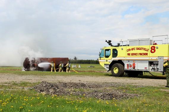 Les pompiers de la Base de Bagotville ont pu utiliser leurs imposants camions autopompe pour éteindre la «carlingue» de l'avion en flammes. Disons que le foin déposé à l'intérieur aidait un peu le brasier... (Le Quotidien, Yohann Gasse)