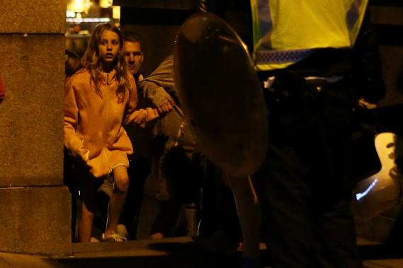 Une fillette au visage pétrifié se réfugie sur le coin d'un édifice près du pont de Londres. (Photo Neil Hall, Reuters)