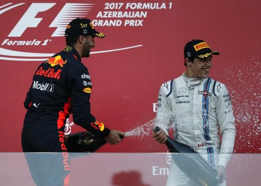 Lance Stroll a eu droit à la douche au champagne, un cadeau de Daniel Ricciardo. (PHOTO DAVID MDZINARISHVILI, REUTERS)