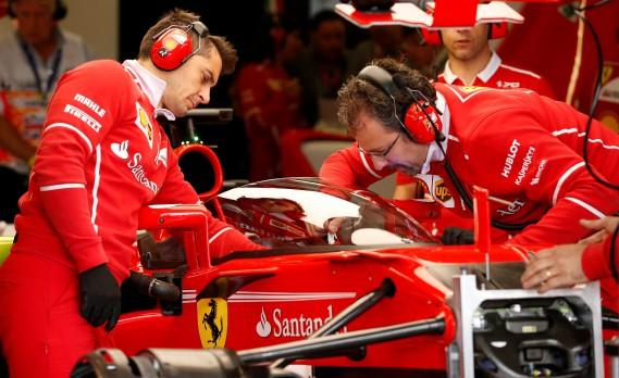 Deux mécanos de l'écurie Vettel au travail sur le pare-brise de protection qui allait être testé un peu plus tard par Sebastian Vettel. (REUTERS)