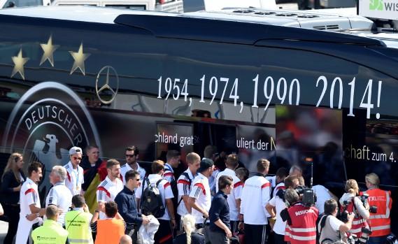 La commandite de l'équipe de soccer d'Allemagne donne une grande visibilité. Ici, les joueurs montent à bord d'un autobus Mercedes peu après être descendus de l'avion les ayant déposés à l'aéroport Tegel de Berlin, le 15 juillet 2014. Cette année-là, l'Allemagne a remorté le Mondial de soccer. (REUTERS)