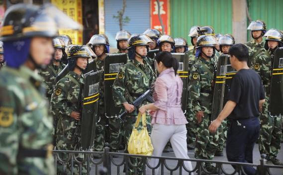 Deux civils chinois traversent un contrôle policier dans une rue d'Urumqi, le 9 juillet 2009, après les violences qui ont fait 200 morts. Les autorités chinoises ont installé une forte présence policière et militaire après ces troubles, qui se maintient encore aujourd'hui. (AFP)