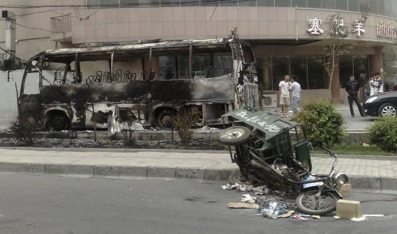 Un triporteur renversé près d'un autobus incendié après la nuit de violence inter-ethnique du 5 juillet 2009 à Urumqi, capitale de la province à majorité musulmane du Xingjiang. , (AP)