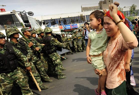 Une femme ouïghoure manifeste avec son enfant dans les bras lors des troubles de 2009. La majorité ouïghoure réclame plus de droits. (AFP)