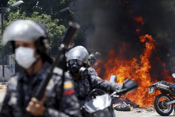 À Caracas, la capitale vénézuélienne, de violents affrontements entre manifestants et forces de l'ordre se déroulaient dimanche sous une pluie de gaz lacrymogènes et de balles en caoutchouc. (AP, Ariana Cubillos)