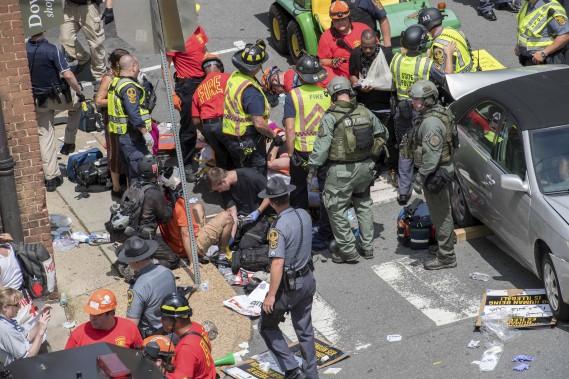 Des gens reçoivent les premiers soins après qu'une voiture ait foncé dans la foule qui manifestait à Charlottesville, samedi. (AFP, PAUL J. RICHARDS)