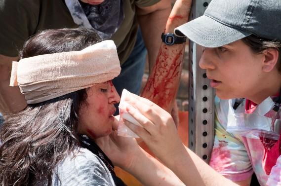 Une jeune femme reçoit les premiers soins aprèsqu'une voiture ait foncé dans la foule qui manifestait à Charlottesville, samedi. (AFP, PAUL J. RICHARDS)
