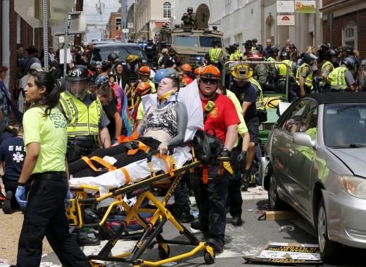 Les secouristes prennent en charge des blessés après qu'une voiture ait foncé dans la foule qui manifestait à Charlottesville, samedi. (AP, Steve Helber)