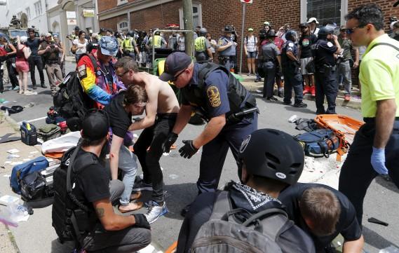 Des gens reçoivent les premiers soins après qu'une voiture ait foncé dans la foule qui manifestait à Charlottesville, samedi. (AP, Steve Helber)