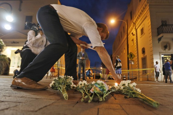 En soirée, samedi, des résidents de Charlottesville ont commencé à déposer fleurs et chandelles sur les lieux où les manifestants ont été heurtés. (AP, Steve Helber)