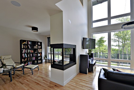 Un foyer au gaz sépare le salon avec toit cathédrale de la salle de lecture, plus intime. (Le Soleil, Patrice Laroche)
