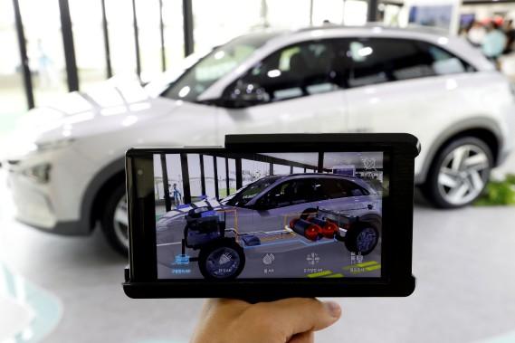 Lors du dévoilement à Séoul, Hyundai utilisait des tablettes de réalité augmentée pour montrer aux journalistes les composantes mécaniques à l'intérieur du futur VUS à hydrogène. (REUTERS)