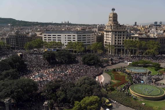 Les gens quittent la Plaza de Catalunya au coeur de Barcelone après avoir observé une minute de slience à la mémoire des victimes de l'attentat perpétré la veille. (AFP, LLUIS GENE)
