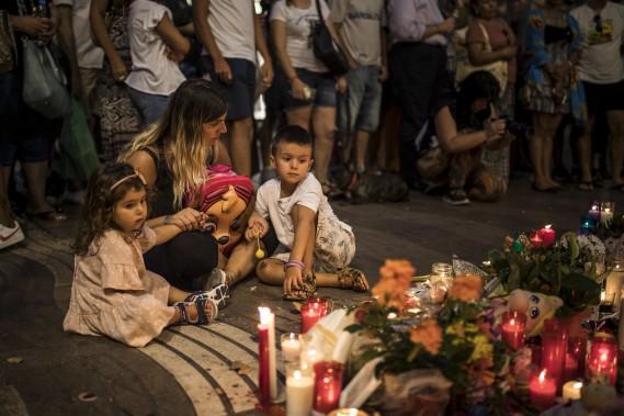 Des gens se sont recueillis à Las Ramblas devant un mémorial pour les victimes de l'attentat perpétré la veille à Barcelone. (AP, Santi Palacios)