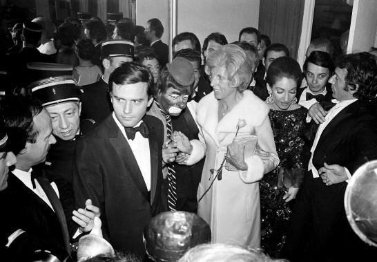 À Paris en avril 1971, déguisé en clown, avec la première dame de France, Claude Pompidou (femme de l'ex-président Georges Pompidou, qui tient une rose. À droite, regardant vers le sol, la chanteuse d'opéra Maria Callas. (AP)