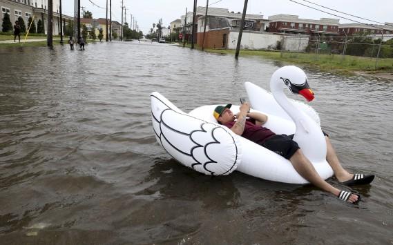 Julio Ostio profite de la montée de l'eau dans les rues du centre-ville de Galveston. (AP, Jennifer Reynolds)