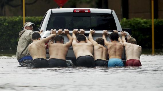 Des gens s'entraident pour pousser un camion à Houston. (AP, Charlie Riedel)