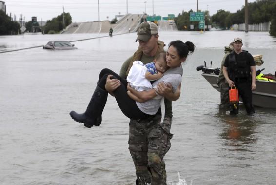 Le policier Daryl Hudeck porte Catherine Pham et son garçon de 13 mois Aiden après les avoir secourus, à Houston. (AP, David J. Phillip)