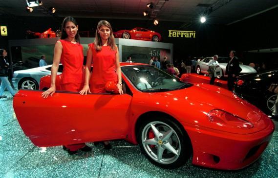 Deux hôtesses posent à côté d'une Ferrari 360 Modena lors du Salon de l'auto Francfort de 1999. (Reuters)