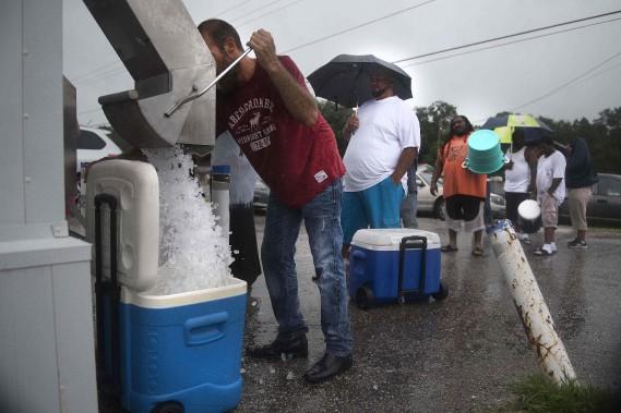 Un bénévole distribue de la glace à des évacués à Tampa. (AFP)