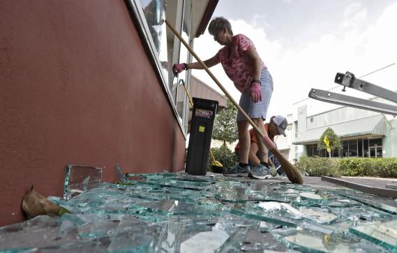 Une femme ramasse la vitre cassée de son édifice. (AP, Chris O'Meara)