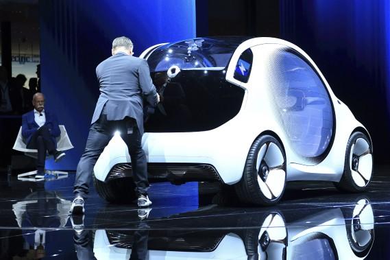 <strong>Court-circuit -</strong> La présentation de la nouvelle Smart électrique a été de mauvais augure. La voiture a eu des problèmes mécaniques et des techniciens ont dû la pousser hors de la scène, sous le regard mécontent de du président Dieter Zetsche, en arrière-plan, à gauche. (AP)