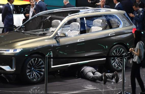 <strong>Journaliste d'enquête automobile -</strong> Un journaliste au sens aiguisé du devoir s'est glissé sous un VUS BMW lors de la première journée des médias au Salon de l'auto de Francfort. (AP)