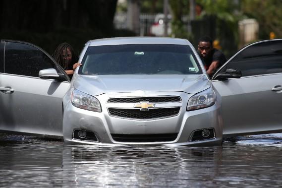 Un couple pousse sa voiture en panne à North Miami le 11 septembre 2017.<br /><br /> (REUTERS)