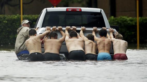 Sept hommes poussent un pick-up en panne dans une rue inondée de Houston le 27 août 2017. (AP)