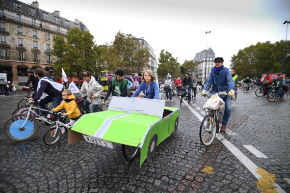 Un enfant pédale sur son véo décoré d'une carrosserie de carton lors de la Journée sans voiture de Paris le 1er octobre. (AFP)