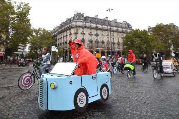<strong>Les vélotomobilistes ont pris la rue à Paris durant la Journée sans voiture -</strong>Cette femme avait confectionné cette voiture en carton montée sur un vélo. Plusieurs des Parisiens aperçus dimanche sur de telles montures avaient préparé leur vraie fausse auto lors d'ateliers organisés par le collectif Vélorution. (Photo : AFP)