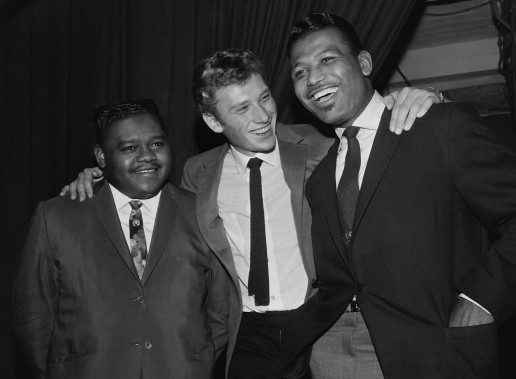 Johnny Hallyday partage un moment avec le pianiste et chanteur Fats Domino (à gauche) et le boxeur Ray Sugar Robinson après un spectacle au Palais des Sports de Paris le 20 octobre 1962. (PHOTO AFP)